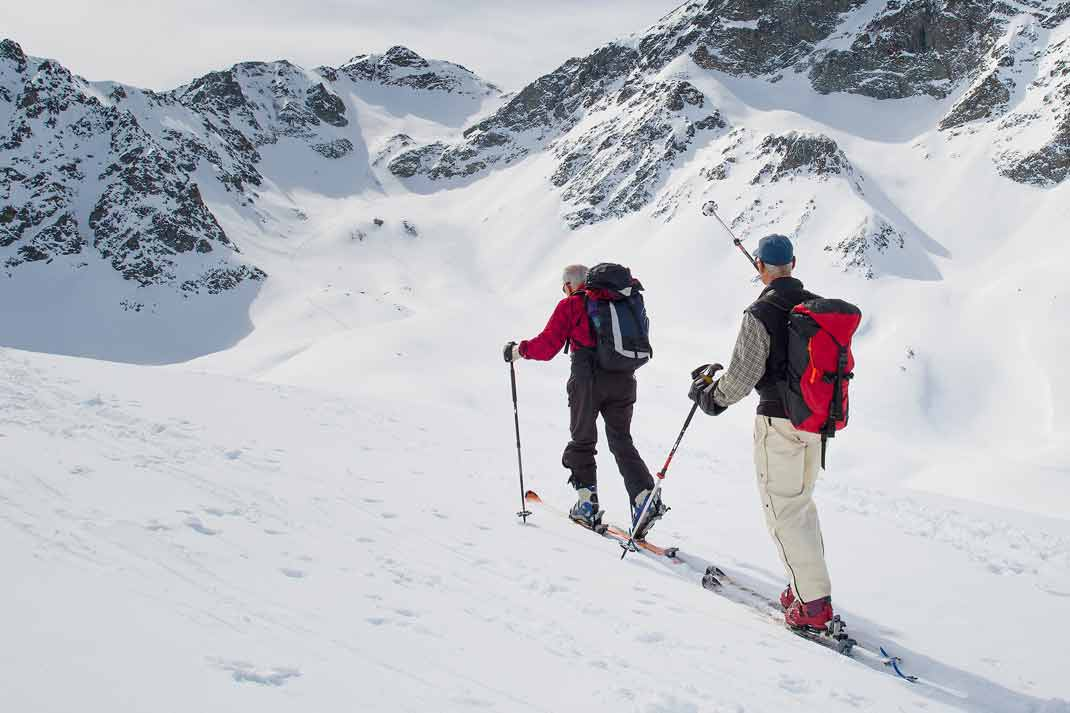 Couple nordic skiing in the wide outdoors with well equipped ski backpacks